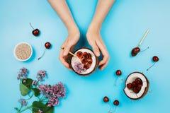 Flatlay用妇女举行一半与基于植物的酸奶碗的椰子的` s手有新鲜的樱桃和chia种子的 库存照片