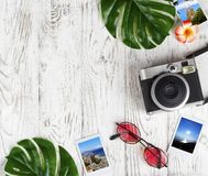 Flatlay с камерой, фото, солнечными очками, листьями на белом столе Стоковые Фотографии RF
