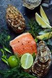 flatlay 新鲜的海鲜的构成在黑暗的背景的 鳟鱼和牡蛎用草本和柠檬 库存图片