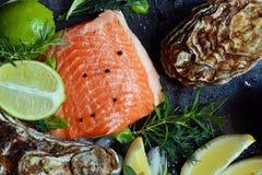 flatlay 新鲜的海鲜的构成在黑暗的背景的 鳟鱼和牡蛎用草本和柠檬 免版税库存照片