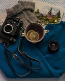 Flatlay of tea with lemons, oldschool camera, sweater and books stock image