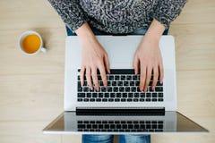 Фрилансер женщины работая на ноутбуке стоковое фото