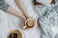 Flatlay acolhedor da mão do ` s da mulher que guarda o chá do limão na cama com folhas e a cobertura brancas foto de stock