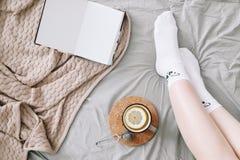 Flatlay acolhedor dos pés da mulher nas meias brancas na cama com camiseta e livro feito malha e um copo do chá do limão fotos de stock