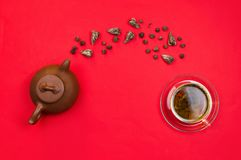 Flatlay arrangement with Chinese clay tea pot and green tea falling into a glass cup. Red background Royalty Free Stock Photos
