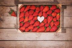 Flatlay ask med nya jordgubbar och en trähjärta Arkivbild