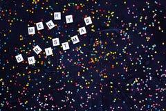 Flatlay av färgrik rund glad jul för för godiskonfettier och text på svart bakgrund Royaltyfri Foto