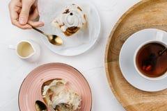 Flatlay av hemlagade kanelbruna rullar med kräm och te arkivbilder