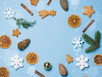 Flatlay of christmas frame decor: gingerbread, snowflakes, fir cones, cinnamon. Copyspace for text, top view. Stock Photo