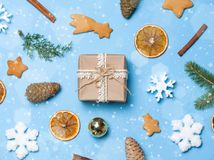 Flatlay of christmas frame decor: gingerbread, snowflakes, gift box, fir cones, cinnamon. Copyspace for text, top view. Royalty Free Stock Images