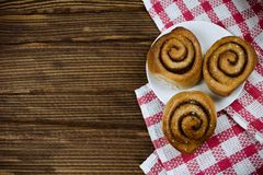 Flatlay with cinnamon rolls on plate on plaid kitchen towel stock photography