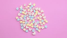Flatlay colorful marshmallows on sweet pink background with copy space. Colorful flatlay marshmallows on sweet pink background, pastel candy color sweet dessert royalty free stock photography