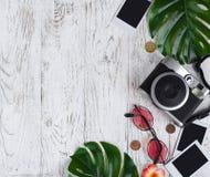 Flatlay com câmera, foto vazia, moedas, óculos de sol, folhas em t Foto de Stock Royalty Free