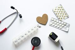 Flatlay composition of medical equipment with wooden heart on white background. Concept of diagnosis, treatment, hospital, patient stock photography