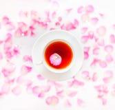 Flatlay con la tazza bianca di tè, le rose rosa, i petali e lo zucchero star fotografia stock