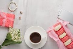 Flatlay con las flores y macarrones, y un teléfono y un regalo con un espacio en blanco para una inscripción en un fondo ligero P foto de archivo