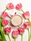 Flatlay con tulipanes rosados y una taza de cacao en un fondo blanco imagen de archivo