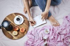 Flatlay confortable avec le blanc a bronzé la femme dans des jeans faisant des notes dans son carnet Photographie stock