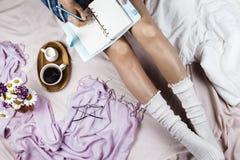 Flatlay confortable avec le blanc a bronzé la femme dans les chaussettes blanches se reposant dans son lit avec la tasse de café  images libres de droits