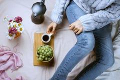 Flatlay confortable de la femme dans les jeans et le chandail se reposant dans son lit Photos libres de droits