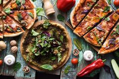 Flatlay of cutted vegetarian pizzas with raw ingredients on shabby blue background. Pesto pizza, Margherita pizza and mushroom. Pizza overhead view stock images