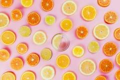 Flatlay cytryny woda na różowym tle z różnorodnymi pokrojonymi cytrus owoc fotografia stock