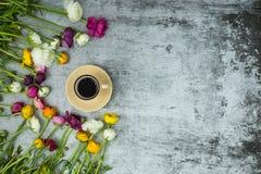 Flatlay de flores da mola e de copo do café preto no fundo de mármore cinzento fotos de stock royalty free