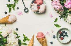 Flatlay de las cucharadas y de las peonías del helado sobre el fondo blanco imagenes de archivo