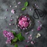 Flatlay de los macarons de la zarzamora en la placa del vintage y la lila florecen imagen de archivo libre de regalías