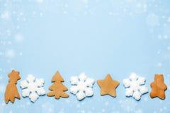 Flatlay des flocons de neige et du pain d'épice sur le fond bleu L'espace libre pour votre texte Vue supérieure image libre de droits