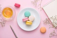 Flatlay des Notizbuches, Kuchen macaron, Tasse Tee und Blume auf Rosa Stockbild
