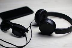 Flatlay des schwarzen Telefons, der Kopfhörer und des Glases lizenzfreie stockfotografie