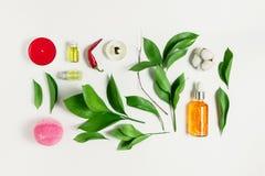 Flatlay des Serums, Parfüm, Badebombe, ätherische Öle mit Ruscus verlässt Lizenzfreies Stockfoto