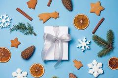 Flatlay des Weihnachtsrahmendekors: Lebkuchen, Schneeflocken, Geschenkbox, Tannenzapfen, Zimt Copyspace für Text, Draufsicht Stockfotos