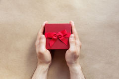 Flatlay-Feiertage giftbox vorhanden in den Mannhänden auf dem Kraftpapier Stockfoto