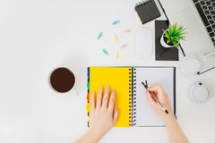 Flatlay with female hands writing in a notepad. royalty free stock photos
