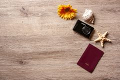 Flatlay ferie/travel tema med brun bakgrund med kameran, passet, skalet, sjöstjärnan och blommor royaltyfri fotografi
