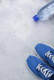 Flatlay folâtre la composition avec les espadrilles et la bouteille bleues de wate Photographie stock