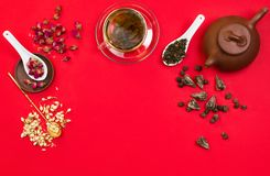 Flatlay frame arrangement with Chinese green tea, rose buds, jasmine flowers and dry tea leaves. Red background. copyspace Stock Images