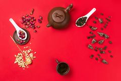 Flatlay frame arrangement with Chinese green tea, rose buds, jasmine flowers and dry tea leaves. Red background. copyspace Royalty Free Stock Photo