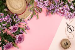 Flatlay frame arrangement with pink chrysanthemum flowers and daisies. Twine, straw hat and scissors, pastel background. Copyspace Royalty Free Stock Photography