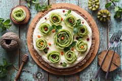 Flatlay of healthy raw gluten free dessert. Homemade tart with kiwi roses, berries, mint and cream filling on nutty crust served. With carved kiwis on shabby stock photo