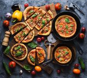 Flatlay of healthy rustic vegetarian pizza party. Homemade pizzas with tomatoes, mushrooms, bell peppers, eggplants and basil in royalty free stock photography