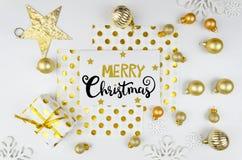Flatlay Hintergrund der Weihnachtskarte mit goldenen Bällen und Beschriftung der frohen Weihnachten der Weihnachtsdekorationen Lizenzfreie Stockfotos