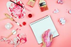 Flatlay med händer för kvinna` som s täckas i målarfärg, borstar, sketchbook och palett och andra tillförsel för konstnär` s royaltyfri foto