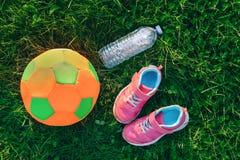 Flatlay med par av rosa flickagymnastikskoskor, bollen för fotboll för barntyg den mjuka och flaskan av vatten i grönt gräs Arkivbilder