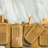 Flatlay of melting coffee latte popsicles, copy space, square crop. Summer healthy vegan frozen dessert. Flatlay of melting coffee latte popsicles over light stock image