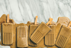 Flatlay of melting coffee latte popsicles, grey background, copy space. Summer healthy vegan frozen dessert. Flatlay of melting coffee latte popsicles over light royalty free stock photo