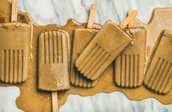 Flatlay of melting coffee latte popsicles on grey background. Summer healthy vegan frozen dessert. Flatlay of melting coffee latte popsicles over light grey royalty free stock images