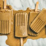 Flatlay of melting coffee latte popsicles on grey marble background. Summer healthy vegan frozen dessert. Flatlay of melting coffee latte popsicles over light royalty free stock images